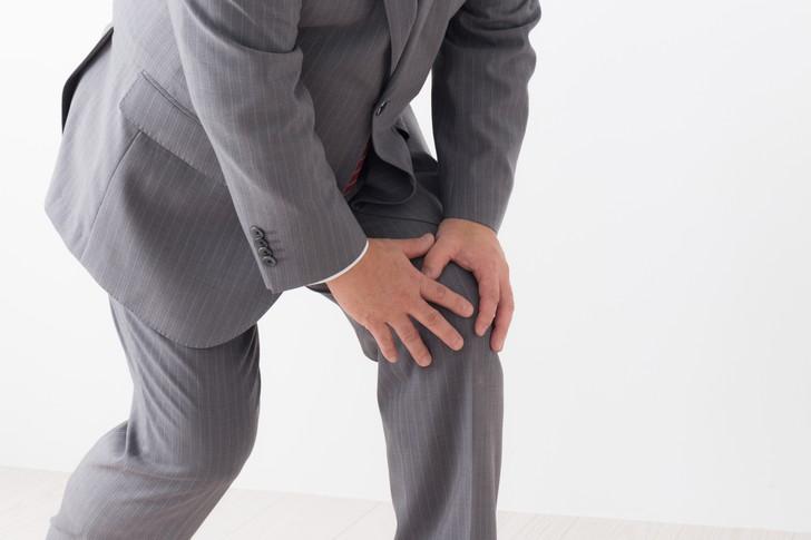 膝をおさえる男性